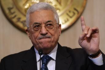 Palestinian leader Mahmoud Abbas holds a