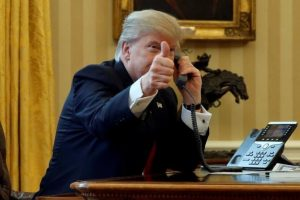 U.S. President Donald Trump gives a thumbs-up to reporters as he waits to speak by phone with the Saudi Arabia's King Salman in the Oval Office at the White House in Washington