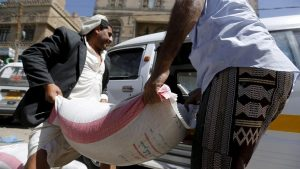 People carry a sack of wheat to a van outside a food distribution center for poor families in Yemen capital Sanaa